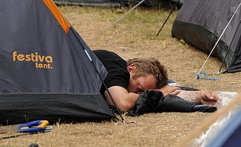 Un campista duerme con la cabeza fuera de la tienda.   Afp