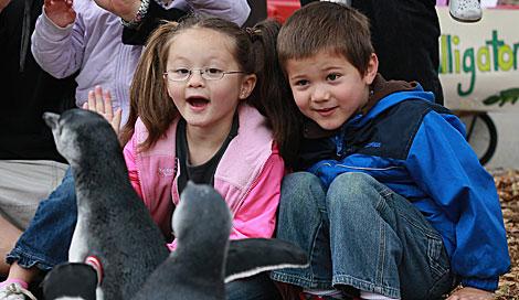 Varios niños juegan con pingüinos.| Justin Sullivan | AFP