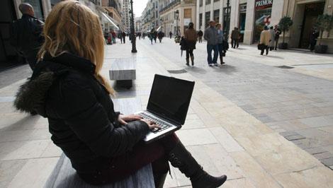 Una mujer usa el portátil en la calle.| Antonio Pastor