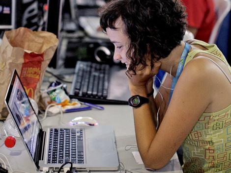 Una chica sonríe mirando a su ordenador. | Elmundo.es