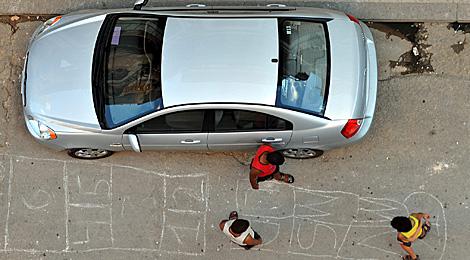 Varios niños juegan junto a un coche.| EFE | Alejandro Ernesto