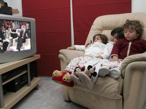 Unos niños miran la televisión. | Esther Lobato