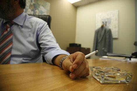 Un hombre fuma en su trabajo.| Ap