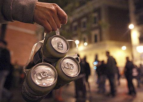 Un joven lleva un pack de cervezas por la noche.| El Mundo
