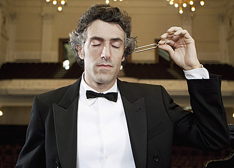 Un director de orquesta escucha un diapasón. | Foto: Olix Wirtinger