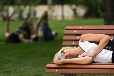 Una señora duerme la siesta en un parque. | P. Armestre