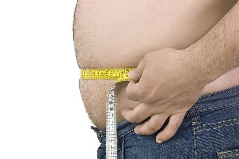 Un varón mide su abdomen con un metro.| El Mundo