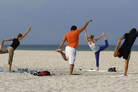 Varias personas hacen ejercicio en una playa.   Afp