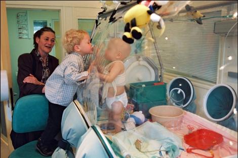 Un niño burbuja recibe la visita de su familia. | Corbis