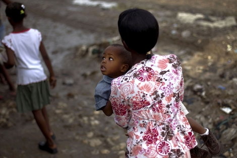 Una mujer camina con su hijo en brazos en Puerto Príncipe.  Ap