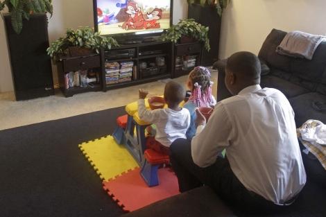 Un padre ve la televisión con sus hijos. | AP