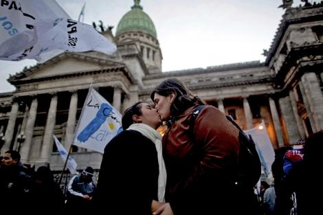 Una pareja se besa frente al congreso argentino. | El Mundo