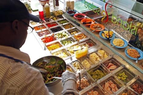 Un empleado sirve un plato en una cadena de comida rápida.| Reuters