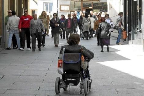 Una mujer pasea en silla de ruedas en medio de una calle peatonal. | R. Blanco