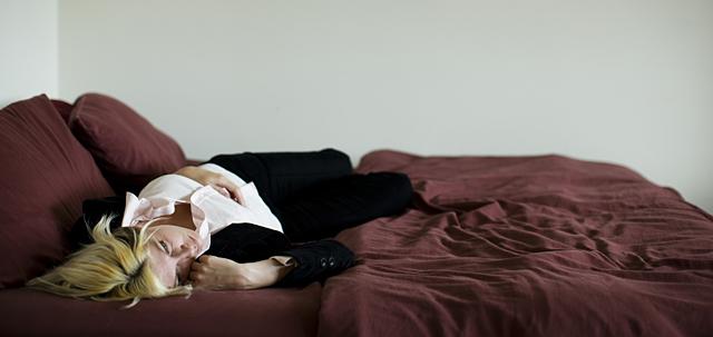 Una joven tumbada en una cama. | Zave Smith. Corbis