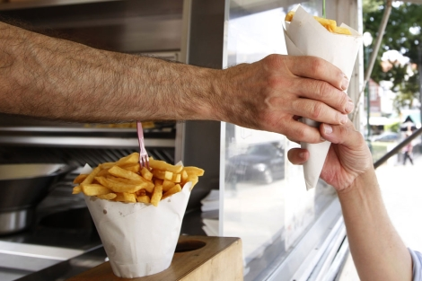 Un niño compra patatas fritas en un puesto callejero. | F. Lenoir