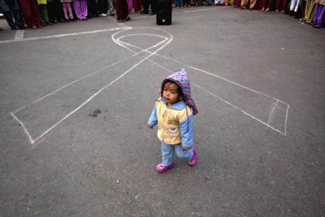 Una niña nepalí camina frente a un lazo contra el sida. | Efe