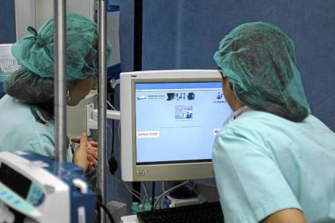 Dos enfermeras consultan el historial de un paciente en turno de noche. | El Mundo