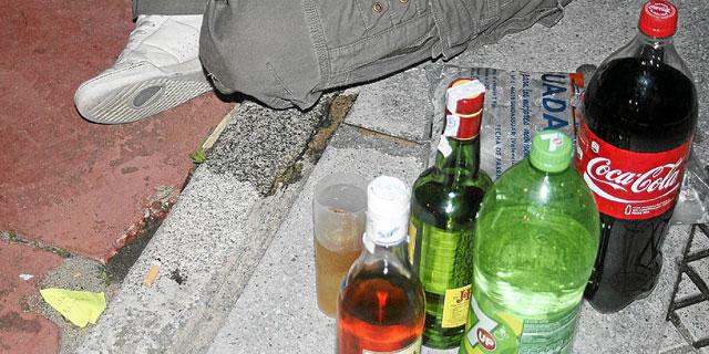 Botellas de alcohol y de refrescos en la acera durante un botellón.| E. Domínguez
