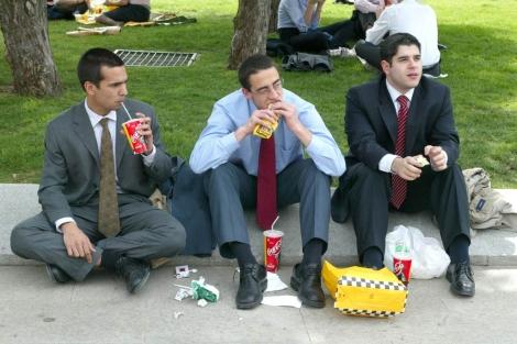 Tres ejecutivos toman comida rápida en un descanso del trabajo.| El Mundo
