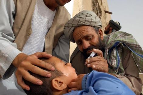 Un trabajador de UNICEF vacuna a un niño en Kandahar.   AP
