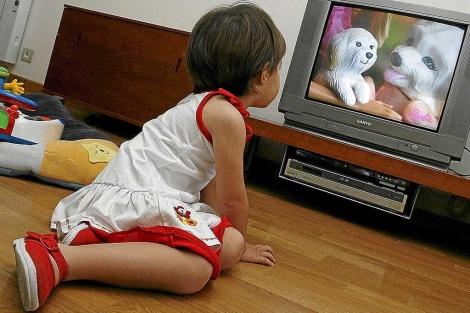 Una niña pequeña ve la televisión.   R. Pérez