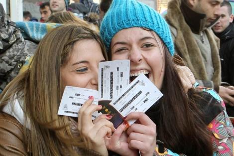 Dos jóvenes muestran su alegría tras conseguir dos entradas de fútbol. | Efe
