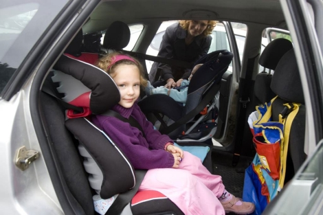 Una familia colocando a los niños en el coche. | El Mundo