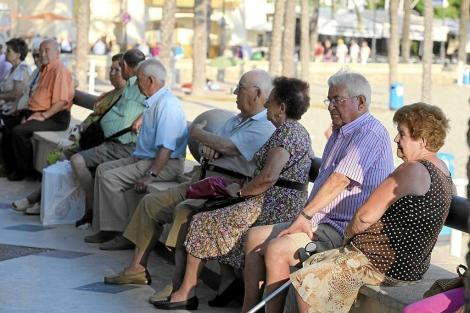 Un grupo de jubilados descansa en un paseo marítimo de Benidorm. | Leslie Hevesi