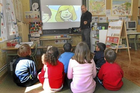 Varios niños atienden las explicaciones de su profesor. | José María Arias