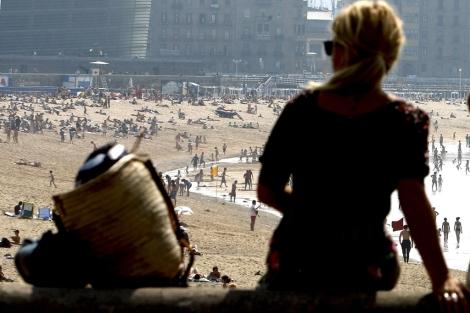 Una mujer se resguarda del sol de la playa. | El Mundo