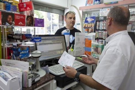 Un farmacéutico de Barcelona atiende a un cliente. | Efe