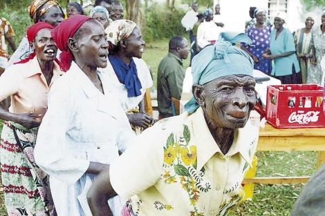 Un grupo de mujeres africanas; al fondo, un caja de Coca-Cola.  Janet Walsh.