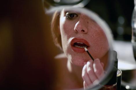 Una mujer se maquilla frente al espejo. | Antonio Heredia