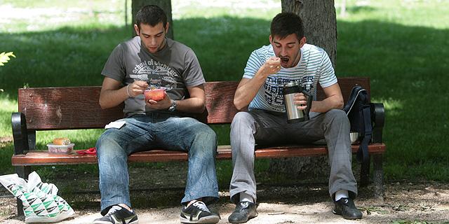 Dos jóvenes comiendo en un parque.  Begoña Rivas