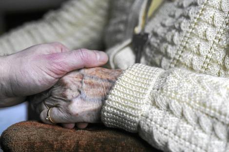 Una mujer sujeta la mano de una anciana con Alzheimer.   Afp