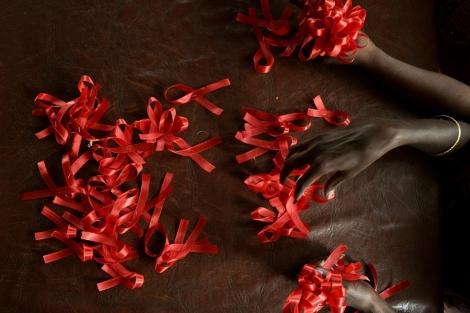 Mujeres seropositivas preparan lazos para el Día Mundial contra el Sida. | Manjunath Kiran | Afp