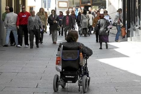 Mujer en silla de ruedas por una calle peatonal. | R. Blanco