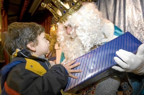 El rey Melchor entrega un regalo a un niño. | J.G. Koch