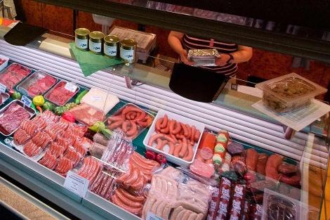 Un mostrador con salchichas, beicon y otros embutidos
