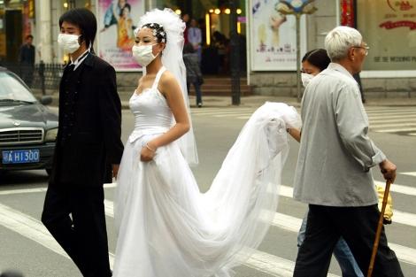 Una pareja de novios cruza una calle con mascarilla