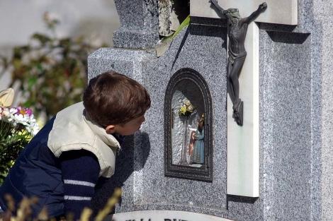 Un niño besa una lápida en un cementerio
