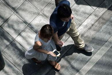 Una mujer consulta internet en su teléfono mientras pasea. | Afp