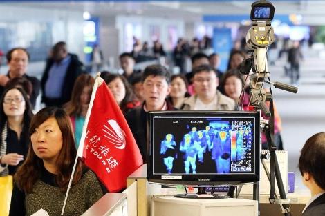 Varios pasajeros pasan por un arco de temperatura en un aeropuerto