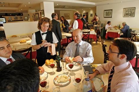 Varios comensales hablan con una camarera en un restaurante