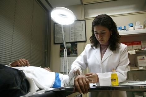 Una doctora atiende a un paciente en Barcelona.| Santi Cogolludo