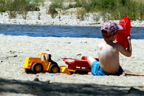Un niño juega mientras toma el sol.| EM