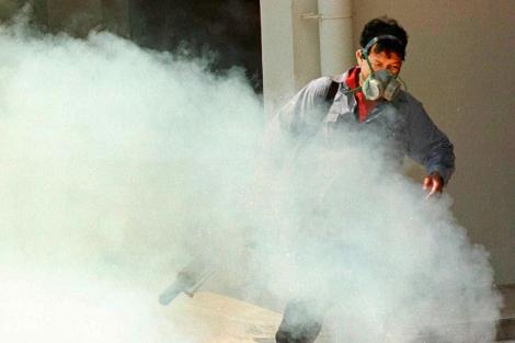 Un hombre fumiga un bloque de apartamentos en Singapur.| Ed Wray | Ap