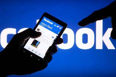 Un usuario con una aplicación de Facebook en el móvil.| Reuters
