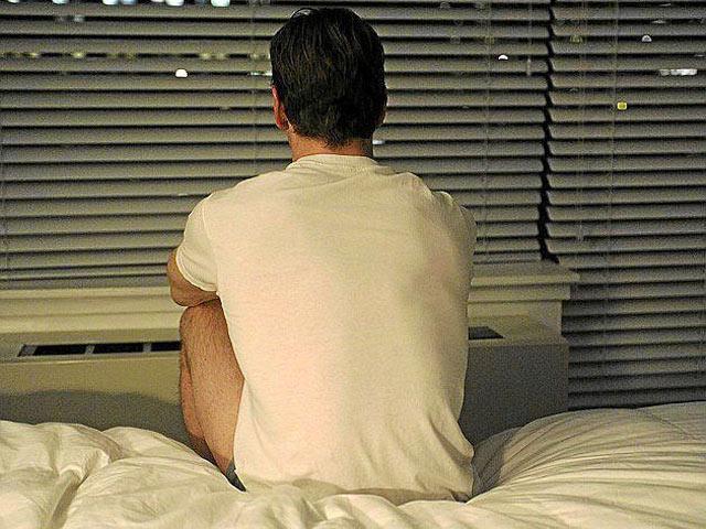 Hombre sentado en una cama de espaldas | Mundo